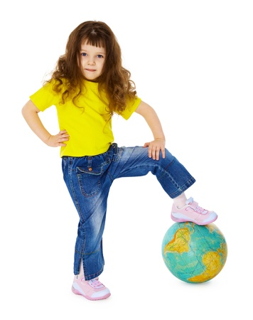 The little girl put her foot on the geographic globe isolated on white background photo