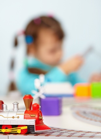 A child playing with a toy railway close up photo