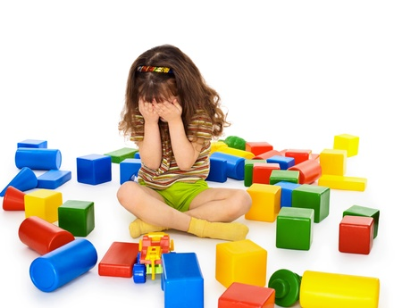 A little girl sitting on a white background among the toys and crying