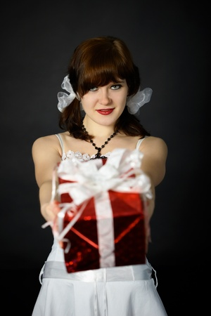 Young attractive woman gives us a gift in red box with a bow on dark background photo