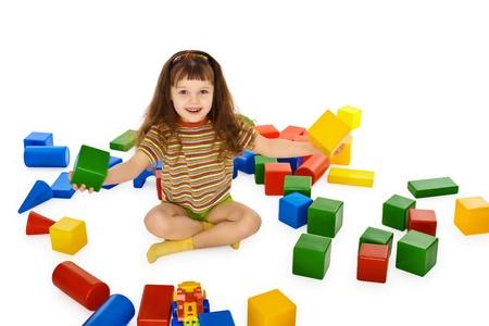 loose hair: Bambina, giocare con i cubi colorati sul pavimento isolato su sfondo bianco