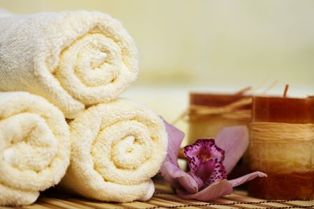 Still-life from towels, a flower and candles on a bamboo mat Stock Photo - 9402227
