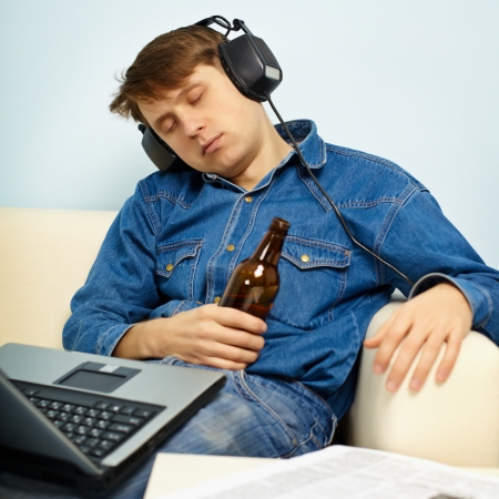 drowsiness: A young man fell asleep at home on the couch with a beer Stock Photo