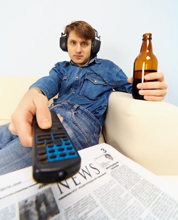 operates: Giovane uomo seduto sul divano a guardare la TV