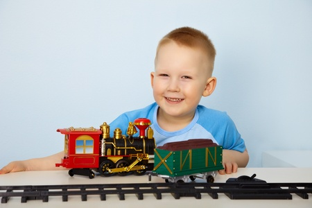 Little boy playing with a toy railway photo