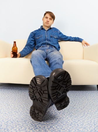 sprawled: Drunk dude sprawled comfortably on the couch with beer