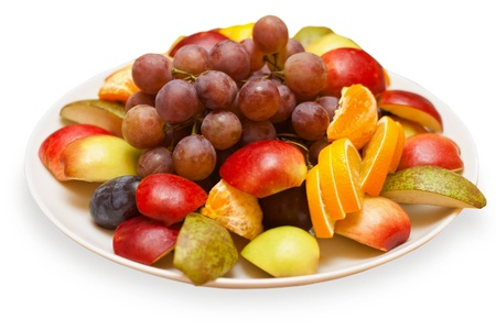 mixed fruit: Cut fruits and grapes on a plate isolated on white background Stock Photo
