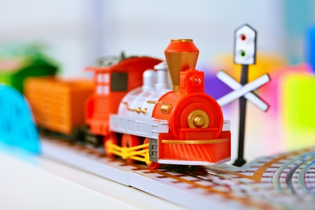 Toy miniature plastic red locomotive on railroad photo