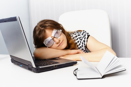 sleeping at desk: A woman sleeps on the job by using fake eyes Stock Photo