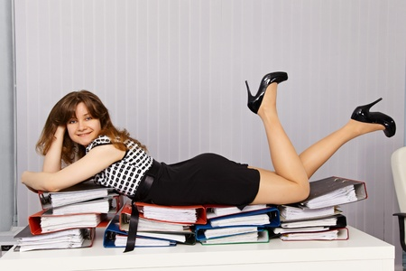 Girl - office worker lay down comfortably on the documents Stock Photo - 10048634