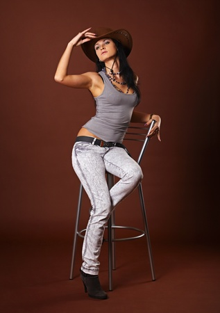 brown leather hat: Beautiful sexy girl in the studio on a brown background