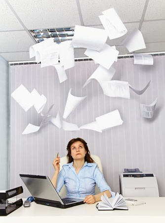 An office worker and annoying, flying documentation Stock Photo