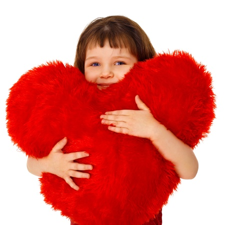 Little girl hugging a large toy heart isolated on white background photo