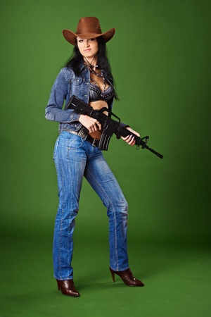 Young beautiful woman in jeans with a rifle on a green background