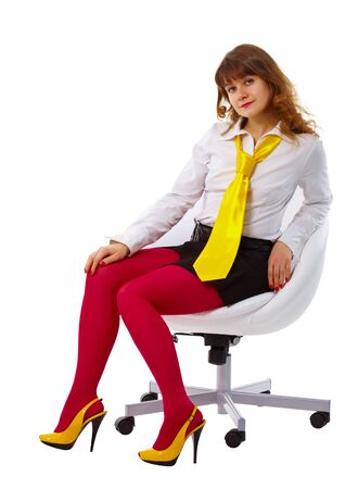 Beautiful young woman in bright clothes sitting in a chair isolated on white background photo