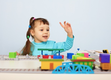 A child plays with a toy railroad on table photo