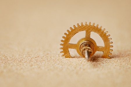 Clock detail - a gear in the sand close up photo