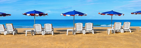 White sunbeds and umbrellas on a tropical beach - panorama photo