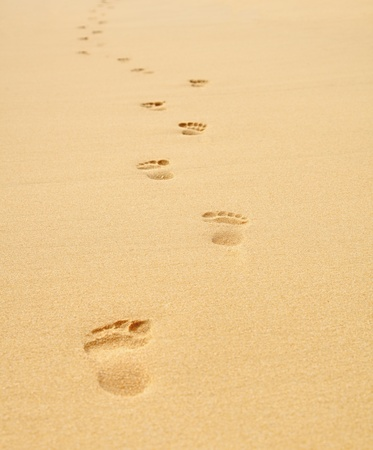 Footprints on the beach stretching into the distance Stock Photo