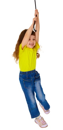 Little girl swinging on a rope isolated on white background photo