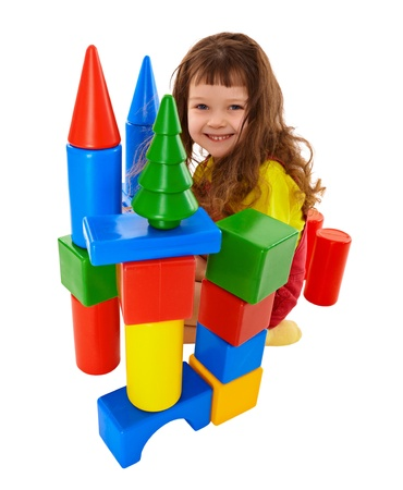 Small child built a castle from color cubes isolated on white background photo