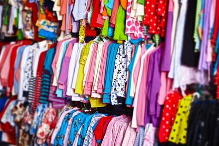 tienda de ropas: Ropa de colores colgados en perchas beb� en una tienda