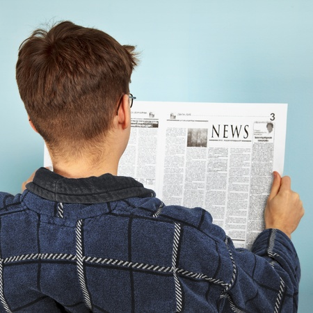 newspaper reading: A man reading the news in the newspaper