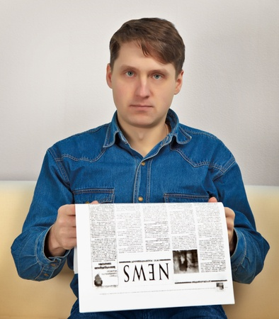 evening newspaper: A man reads evening newspaper at home on the couch Stock Photo