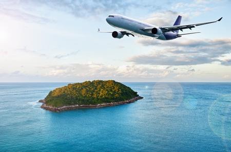 A passenger plane flies over tropical island