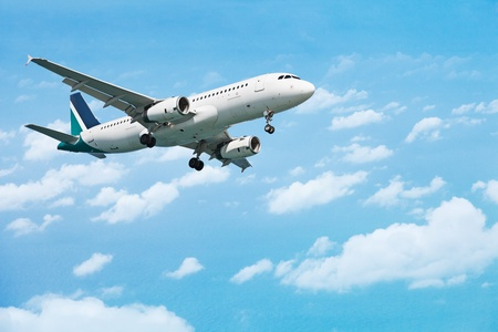 Airliner comes in to land on the background of the cloudy sky