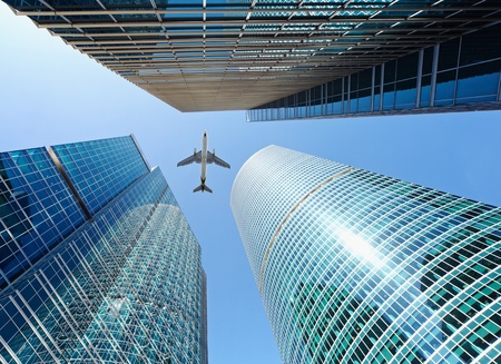 Airliner flying over high-rise buildings - skyscrapers Standard-Bild