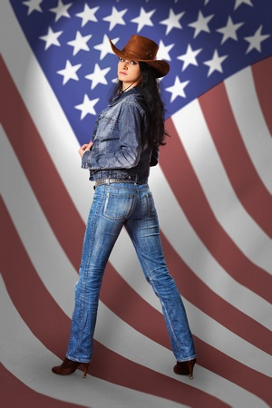 Beautiful young woman in a denim dress and a cowboy hat on a background of the American flag photo