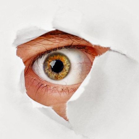 broken through: The eye looks through a hole in the paper - a spy