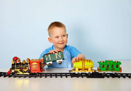 Boy playing with toy railroad at table photo