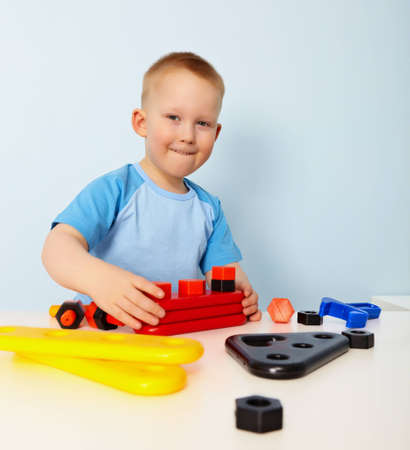 siting: A little boy sitting at a table. Playing Stock Photo