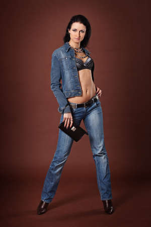 top: Beautiful fashionable girl in jeans on a brown background