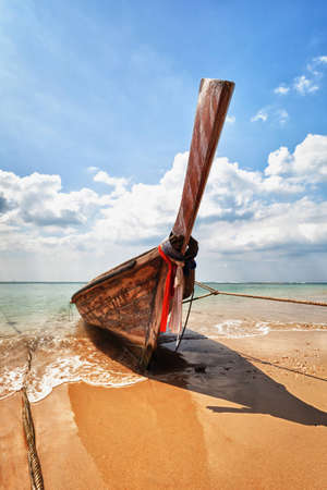 Old wooden traditional boat on the tropical beach - Thailand photo