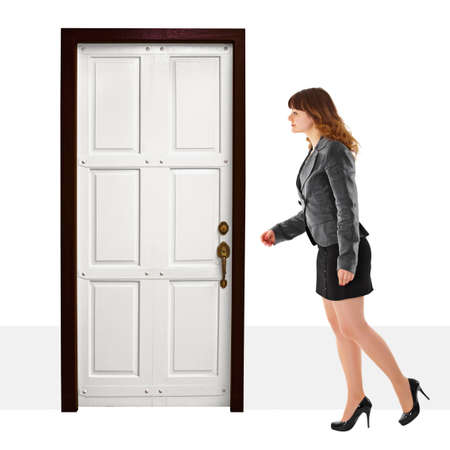A young woman walks into door on white background Stock Photo