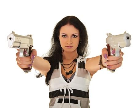 mujer con pistola: Joven mujer posando sobre un fondo blanco con dos pistolas