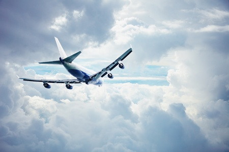 Passenger airliner flying through the thick clouds Stock Photo