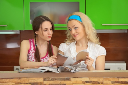 Two girlfriends leaf through womens magazines on kitchen photo