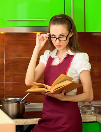 Young beautiful girl reading a cookbook on kitchen photo