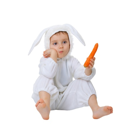 A child dressed as a rabbit with a carrot isolated on white background photo