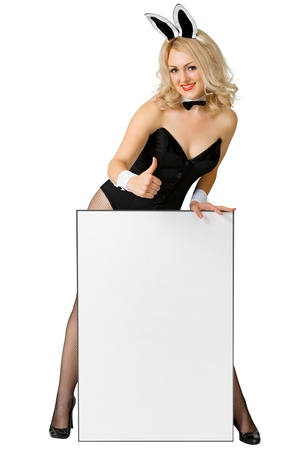 Sexy girl dressed as a playful rabbit with a poster isolated on white photo