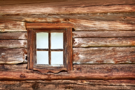 A small window in the wall of an old wooden house photo