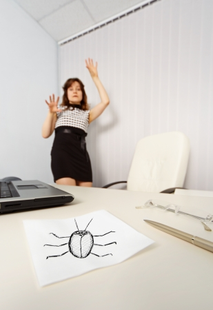 The woman was frightened drawn cockroach in the office photo