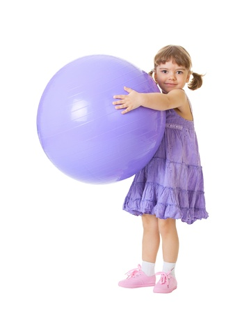 Little girl with a big purple ball isolated on white background photo