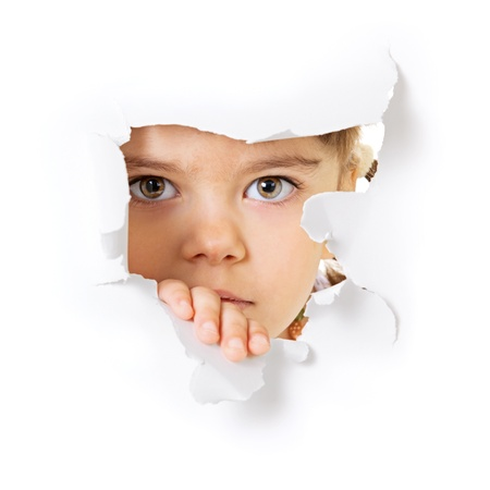 Face of the child looking through a hole in the white paper Stock Photo