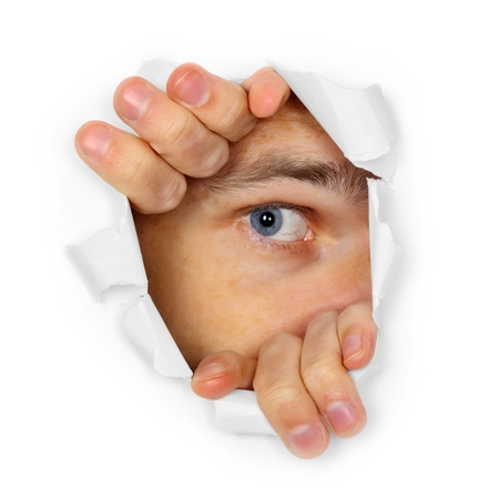 Een man kijkt door een gat in het papier Stockfoto