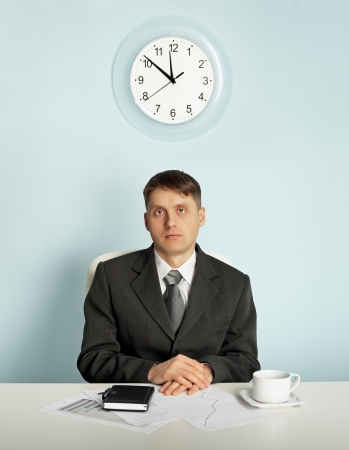 Businessman sitting in an office at the workplace - waiting photo